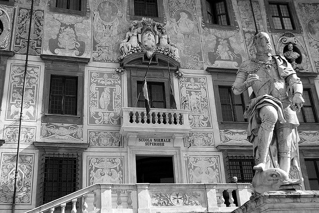 Detail of the façade of the Scuola Normale Superiore with the statue of Cosimo de' Medici in the foreground.