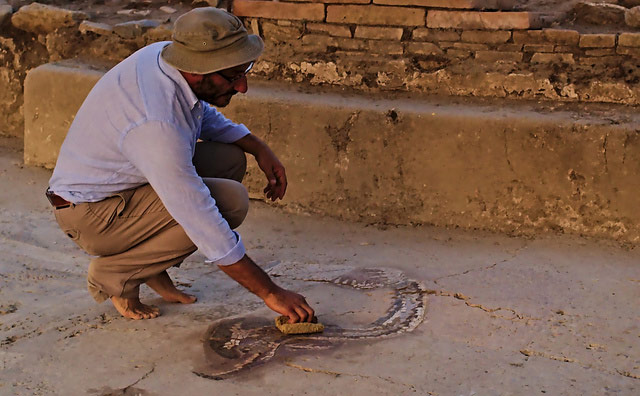 The archaeologist Francesco Cuteri uncovering one of the largest mosaics found dating from the Hellenistic period to the end of the 4th century BC. The mosaics, which cover an area of 35 square meters approximately, were discovered in July 2013 in the ruins of what was to be a spa hotel.