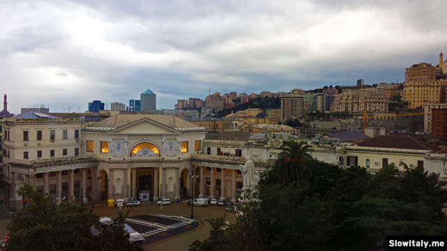 View from our hotel room over Piazza Principe (see at the end of the article). The building that looks like an opera house is the railway station! In front is the statue of Christopher Columbus and on the left in the background, the Lanterna, emblem of Genoa. Photo © Slow Italy.